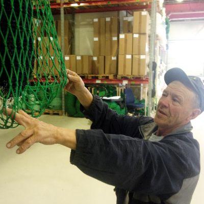 Ove Nysund visar fiskodlingsutrustning som trots tjocka rep kan slitas sönder av de listiga sälarna.