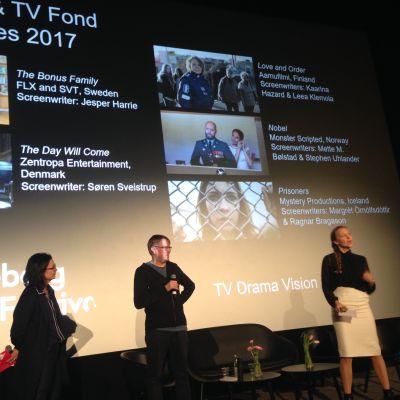 Kolme henkilöä seisoo lavalla.