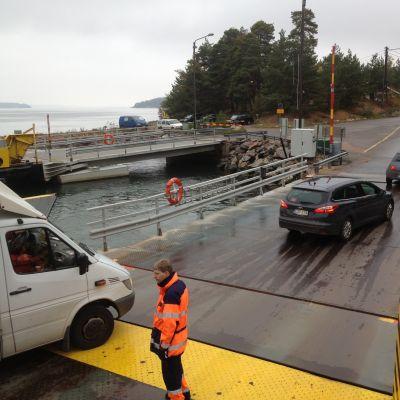 Färjkarl på landsvägsfärjan Sterna övervakar bilarna som kör av färjan i Lillmälö på Pargassidan.