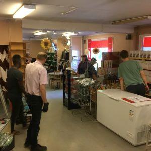 Människor i en gammal butikslokal. De ställer i gång för veckans matutdelning vid mathjälpen.