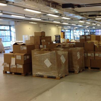 Stora kartonglådor i en lagerhall syns på Tullens bild.