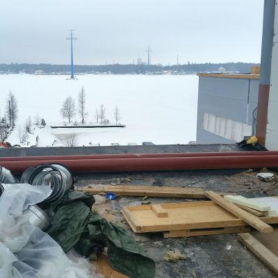 På taket till ett bygge, bräder, rör och plast på taket, utsikt mot Brändö sund i Vasa