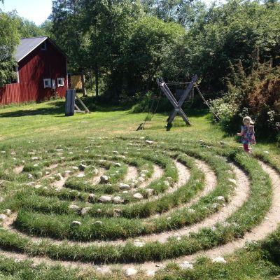 En liten flicka i sommarklänning springer runt jungfrudansen vid Rosala Vikingacentrum.