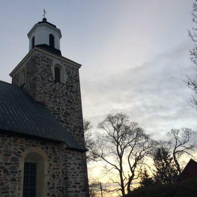 Kimito kyrka med himmel och kyrktorn i fokus.