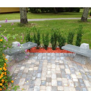 Två små stenbänkar och planteringar i en park.