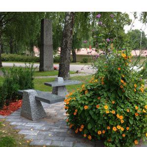 Stenbänkar och planteringar i en park. I bakgrunden en minnessten.