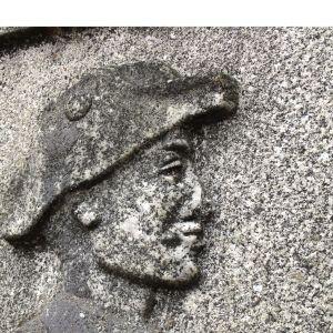 En relief som föreställer en soldats huvud i profil.