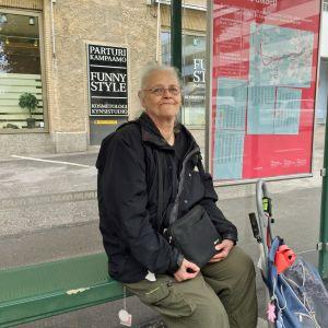 Carita Turunen, en kvinna med vitt hår och glasögon sitter på en busshållplats på Drumsö. Hon har en shoppingkärra bredvid sig och en handväska i famnen.