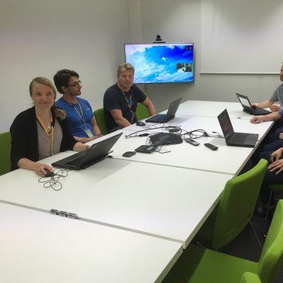 Kuusi insinööriä pöydän ääressä