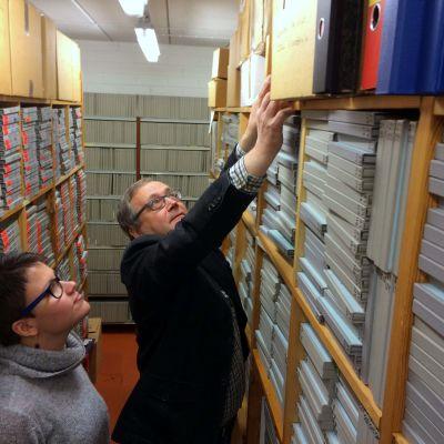 Yle arkiston esimies Janne Ranta nostaa laatikollisen postikortteja musiikkiarkisto Japan amanuenssin Maaret Storgårdsin tutkittavaksi.