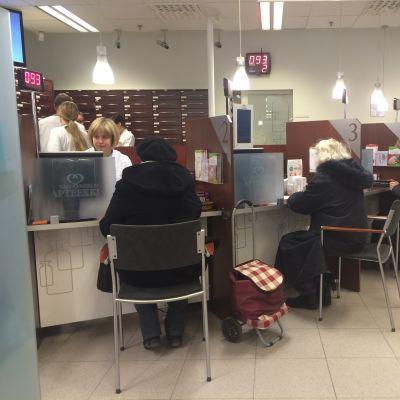 Asiakkaita istumassa apteekin palvelupisteillä.