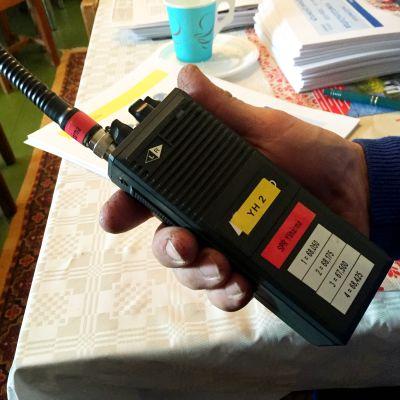 VHF-puhelin miehen kädessä.