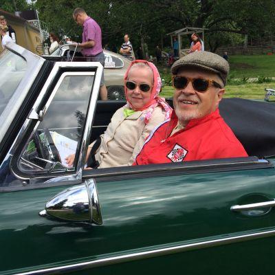 1960-luvun asuihin sonnustautunut pariskunta istuu samalta aikakaudelta olevassa autossa.