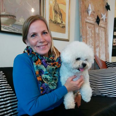 Lea Petäjäaho istuu sohvalla Vuokko-koira vieressä.