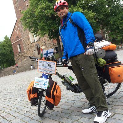 Intialainen mies seisoo polkupyöränsä vierellä Turun tuomiokirkon edustalla.