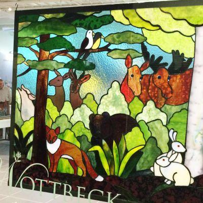 Metsää ja metsäneläimiä kuvaava lasityö ripustettuna näyteikkunaan.