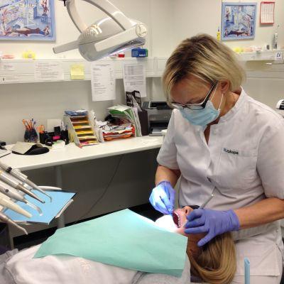 Suuhygienisti tarkastaa tytön hampaiden terveyden