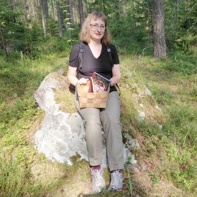Ina Ruokolainen korin ja ruokakirjansa kanssa sienimetsällä.