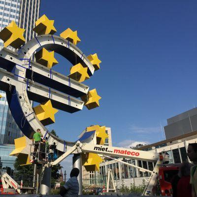 Eurorahan symbolia korjataan Euroopan keskuspankin edessä.