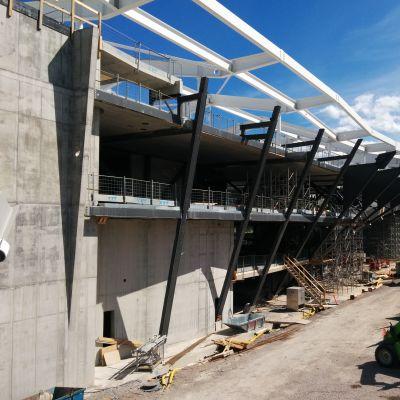 Kuvassa on rakenteilla olevan Keskustakirjaston julkisivun teräksestä ja betonista valmistettu runko. Keskeltä runko kaartuu hieman ulospäin.