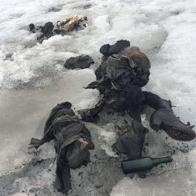 Jäätikön jäässä vanhanaikaiset vaellussaappaat ja lasipullo sekä vanhanaikaisen näköisiä vaatteita.