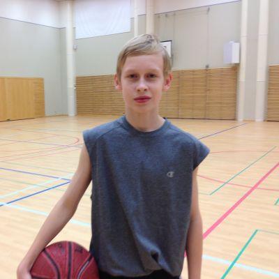 Oscar Storgård stor i en gymnastiksal med en basketboll under armen.