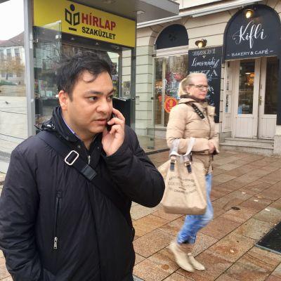 Attila Babos talar i telefon medan han står på gatan i den ungerska staden Pecs