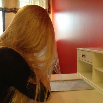 En kvinna sitter vid en tom byrå
