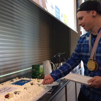 Paralympiavoittaja Matti Suur-Hamari leikkaa mitalikakkua Pajulahden urheiluopistolla.