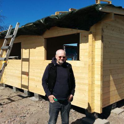 Rakennustöitä vetävä Matti Kinnunen seisoo uuden hirsisaunan edessä aurinkolasit päässä.