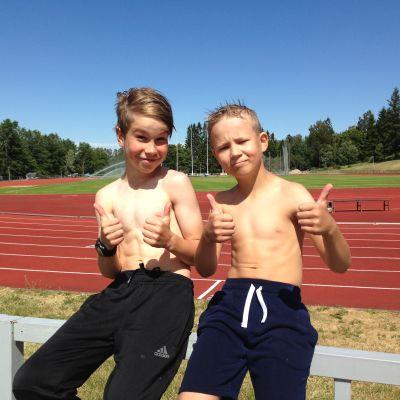Kaksi poikaa istuu urheilukentän aidalla.