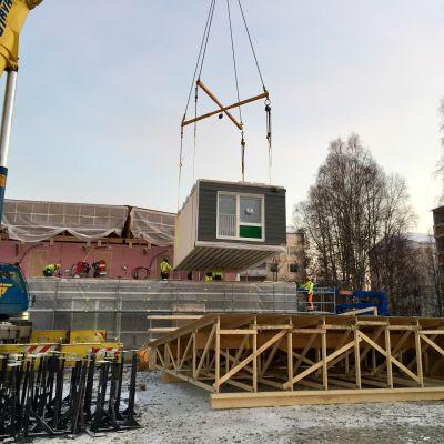 Rovaniemellä Domus Arctican puukerrostalo Kelo pinotaan asuntomoduuleista. Nosturi nostaa Kuhmossa asumisvalmiiksi tehtyä opiskelijayksiötä paikalleen 28.11.2018.
