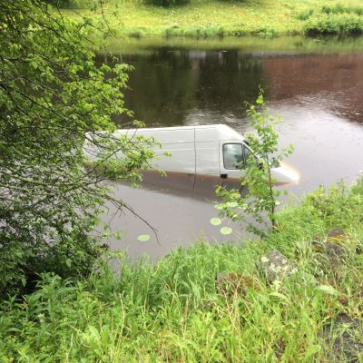 Hopeanvärinen pakettiauto kelluu Kyrönjoessa.