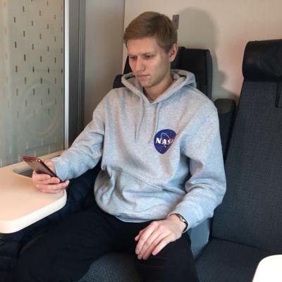 Alexis Aronen lukee kännykkää junassa