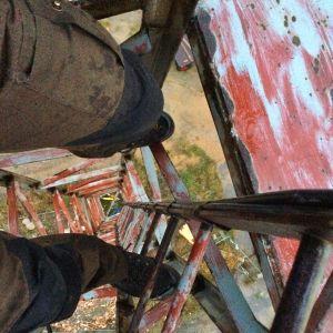 Bild av benen av en man som klättrat högt upp i ett torn och tittar neråt.