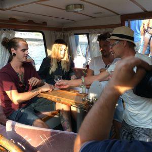 Organisatören av Pernå fiskargilles sommarfest Toni Mankonen bjuder på vin i sin båt vid Sandö, Lovisa