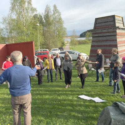 En grupp mänskor står och övar rörelser på en gräsmatta. En ledare (regissör) strö framför dem och ger instruktioner.