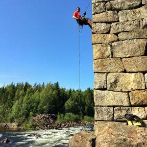 En man som klättrar upp för en stenmur med hjälp av klättringsutrustning, intill en fors.
