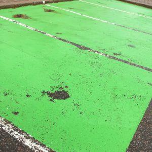 Sliten beläggning på grön parkeringsruta