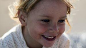 kouluikäinen lapsi hymyilee