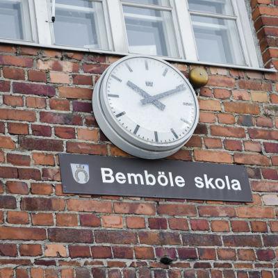 Klocka på vägg, under den skylt med texten Bemböle skola.