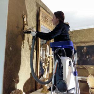 Konstkonservatorn Anna Lehikoinen rengör en ljuslampett med pensel och damsugare.