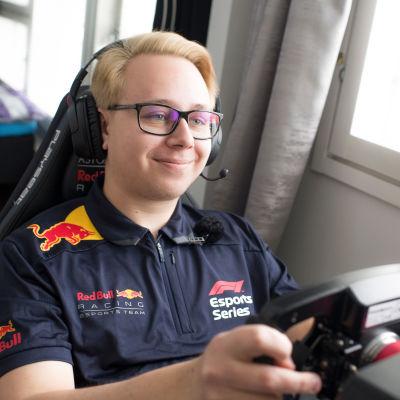 En ung man med ljust hår och glasögon sitter i en stol och håller i en ratt för ett datorspel.