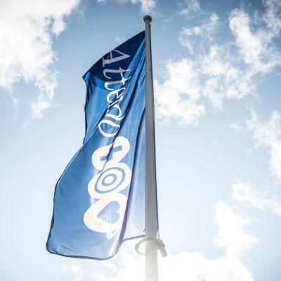 En blå flagga med Attendos logo vajar i en flaggstång. I bakgrunden syns blå himmel med ett lätt molntäcke.