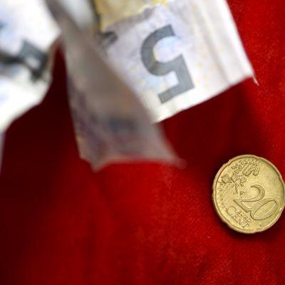 Rypistyneitä viiden euron seteleitä ja 20 sentin kolikko.