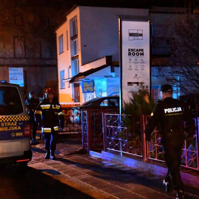 Kuvassa yönäkymä pakohuoneen ulkopuolelta. Poliisit kävelevät Escape Room-kyltin ohi.