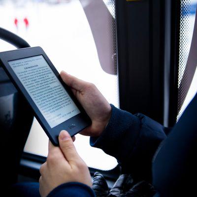 E-kirjan lukulaitteet ovat pieniä ja kevyitä. E-kirjaa luetaan linja-autossa.