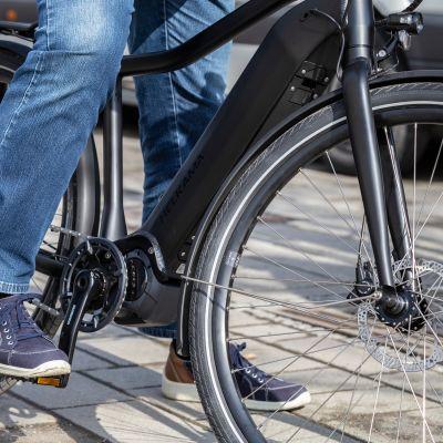 Pyöräilijä on pysäntynyt sähköpyörällä odottamaan kadun ylittämistä. Kuvassa näkyvät pyörä ja kuljettajan jalat.