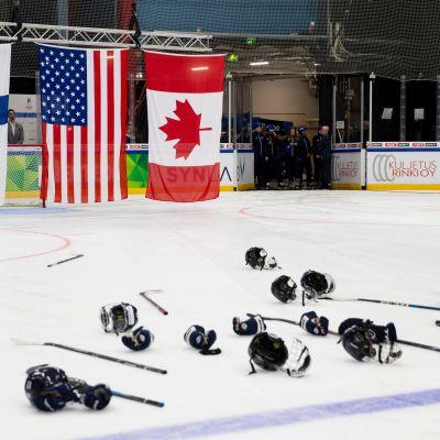 Jääkiekon naisten MM, liput nousee kattoon ja varusteet jäällä.