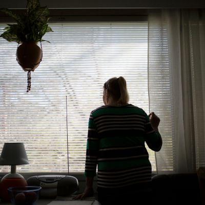 Nainen katsoo ulos ikkunasta